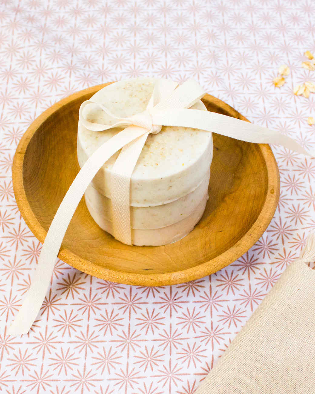 three bars of oatmeal soap stacked and tied with a bow