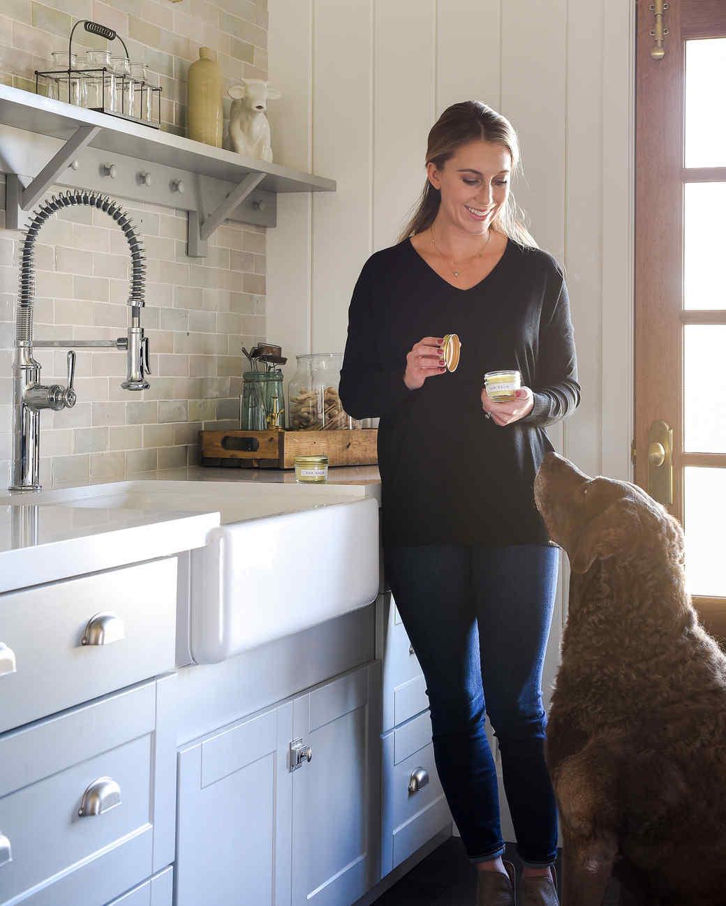 woman holding pet paw balm next to sitting dog