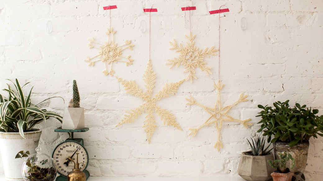 crochet snowflakes on white wall above mantle