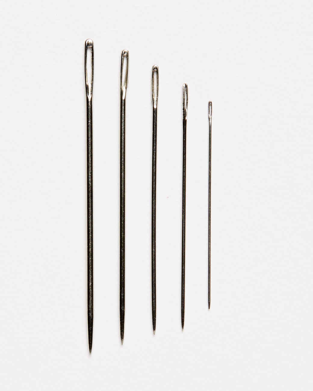 five various sizes of embroidery needles against a white background