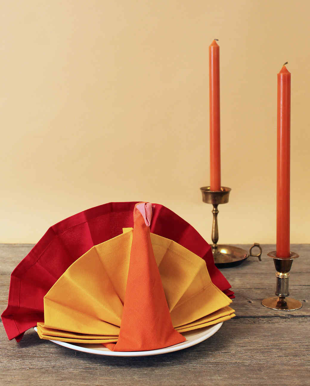folded turkey napkins with two candles on table