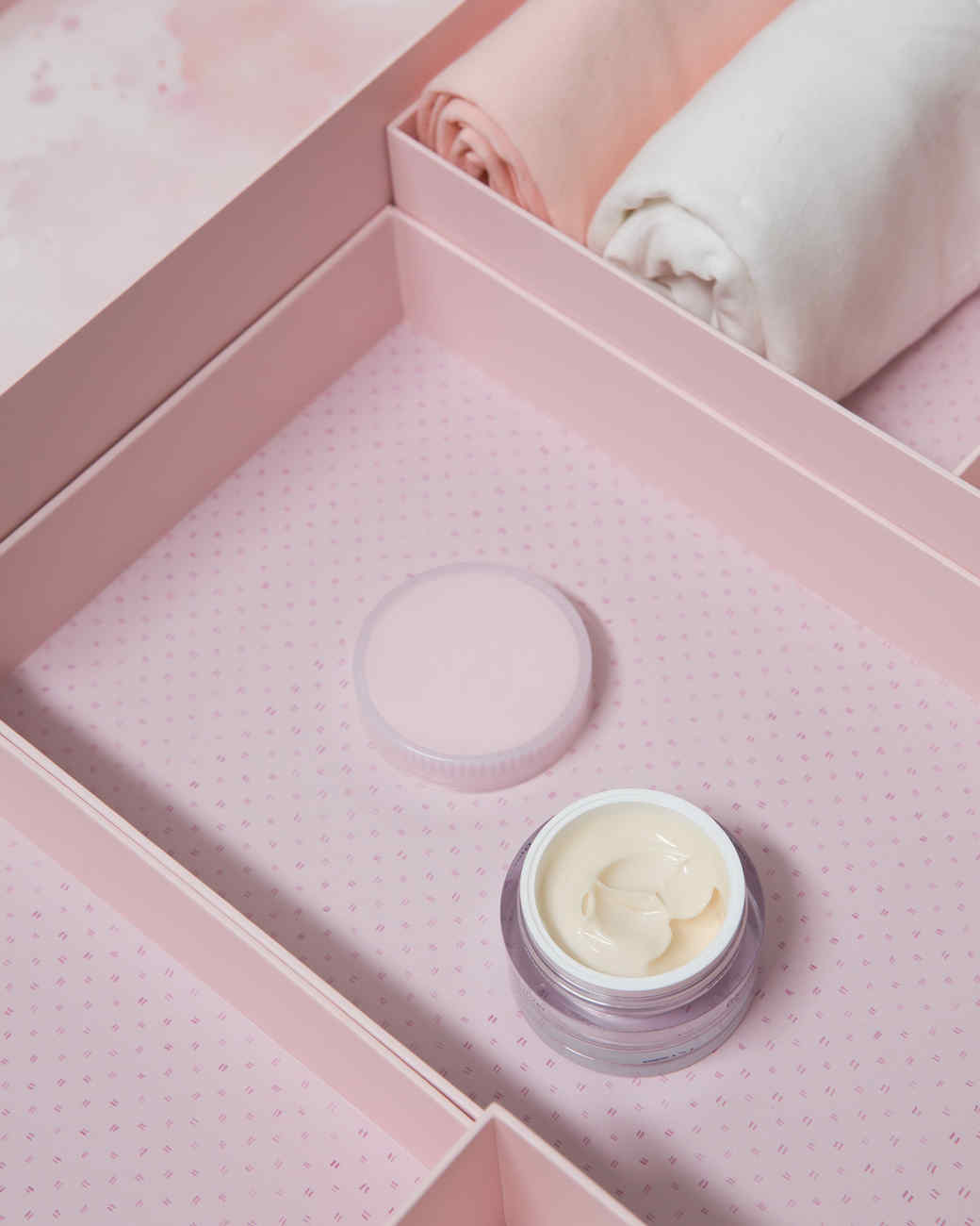 pink marie kondo box holding makeup and rolled clothes