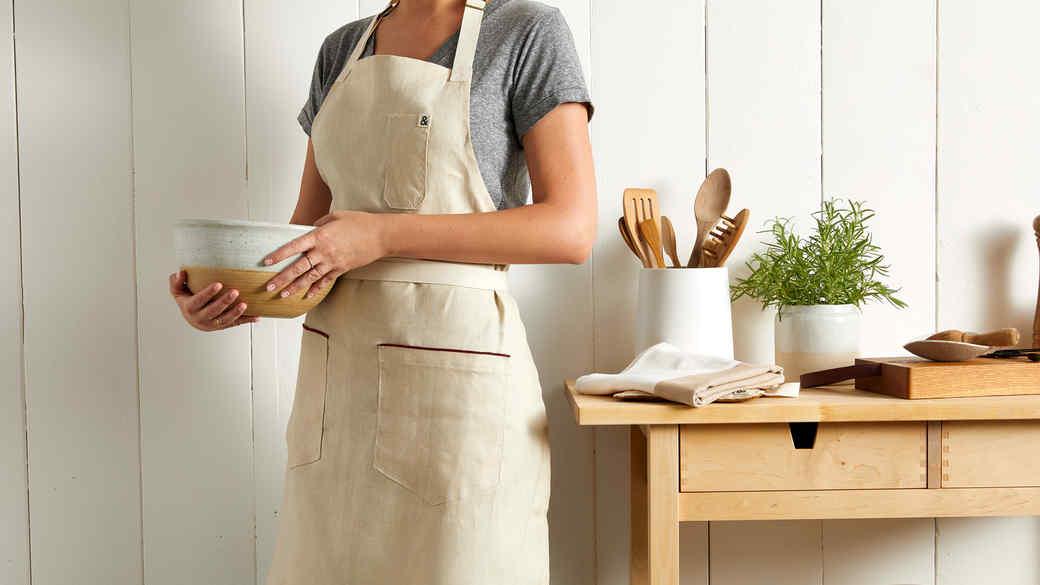 woman in tan apron holding ceramic bowl