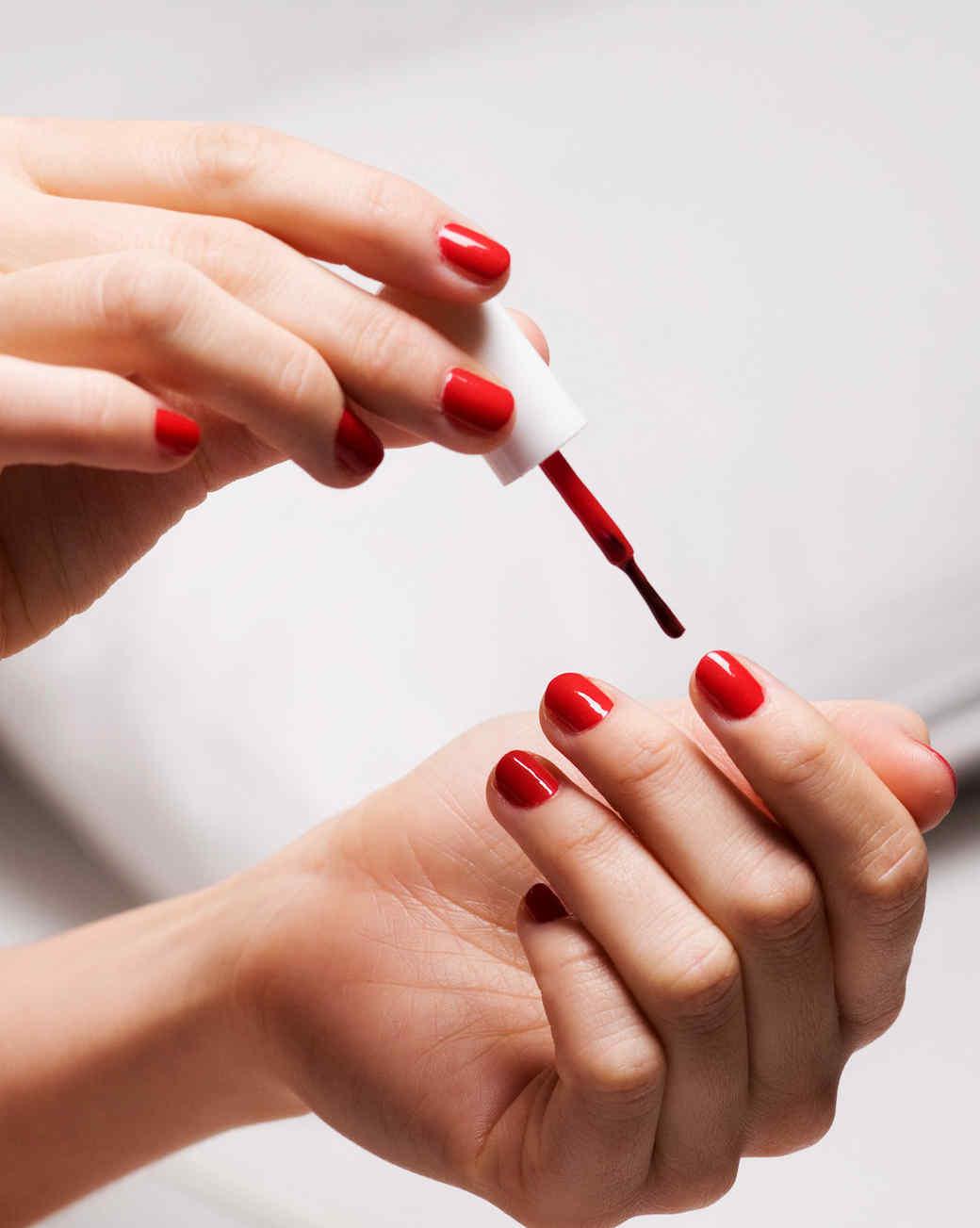 woman painting nails red nail polish