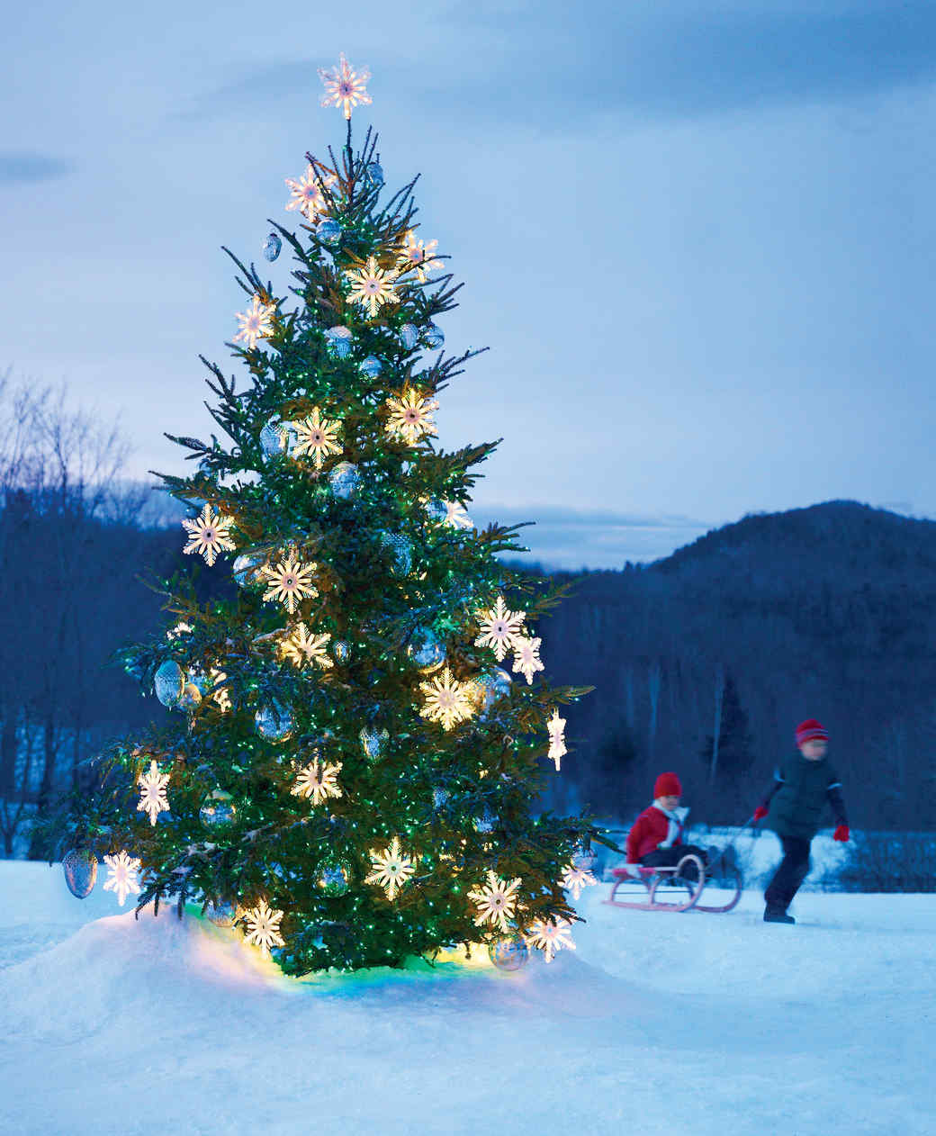outdoor christmas tree with snowflakes glass balls and string lights