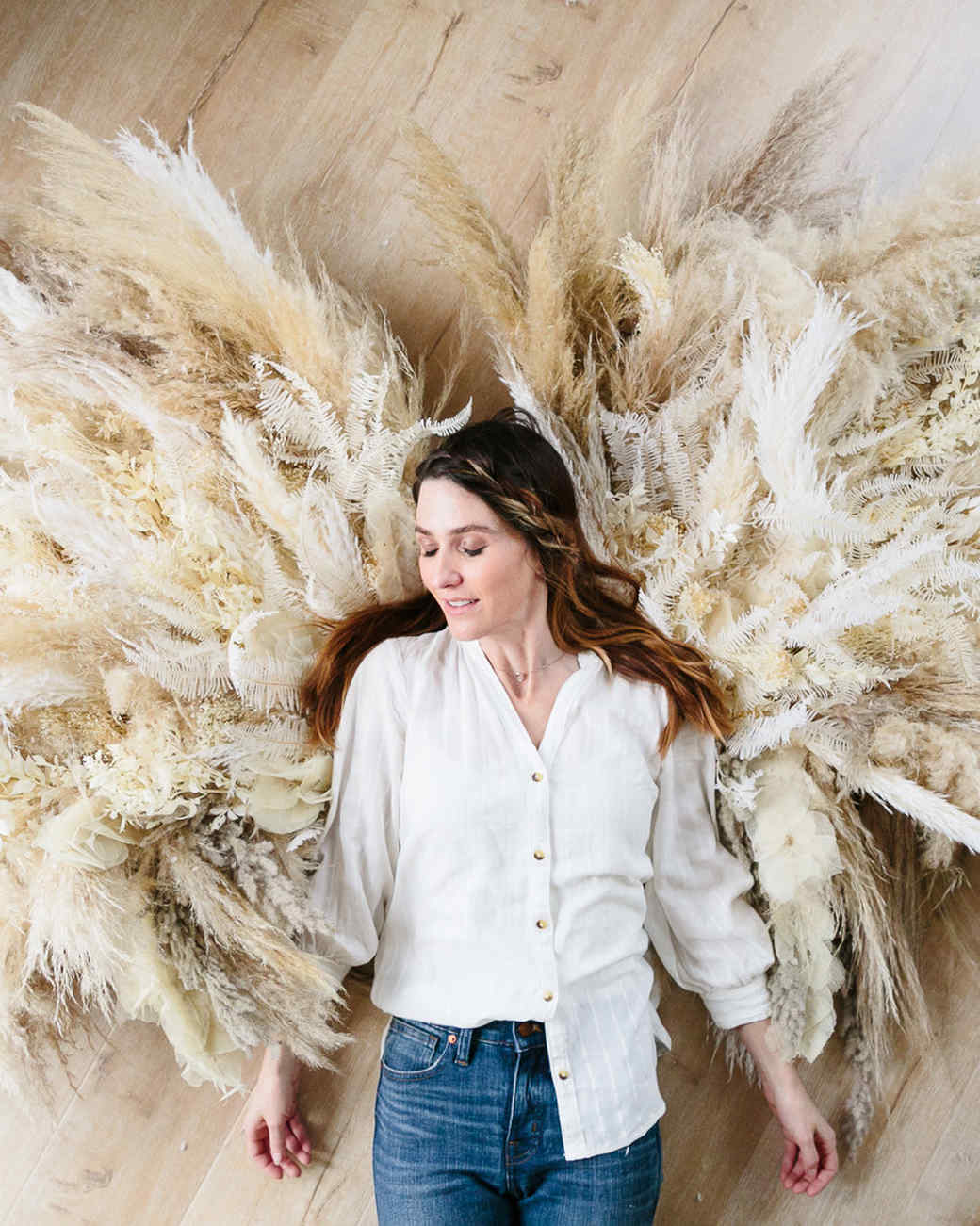 woman laying against pampas grass angel wings