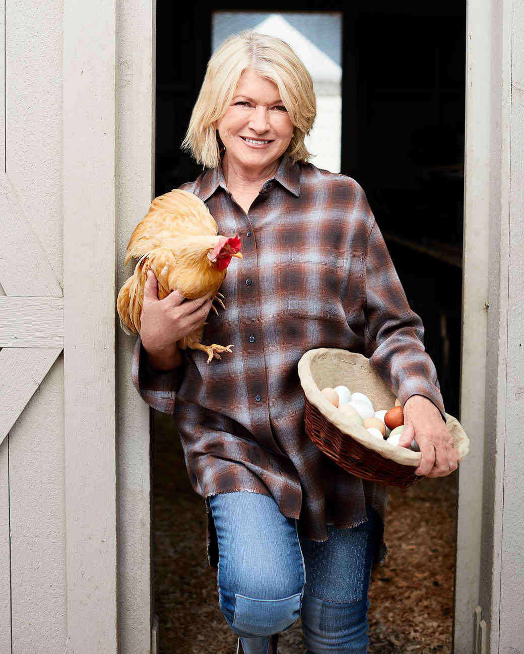 martha holding chicken outside coup