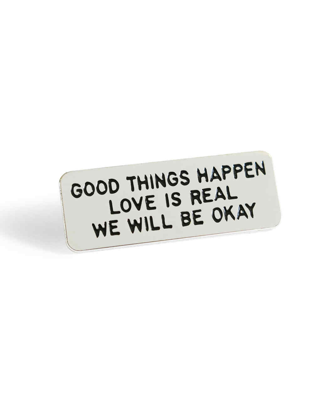 silver pin with positive phrases