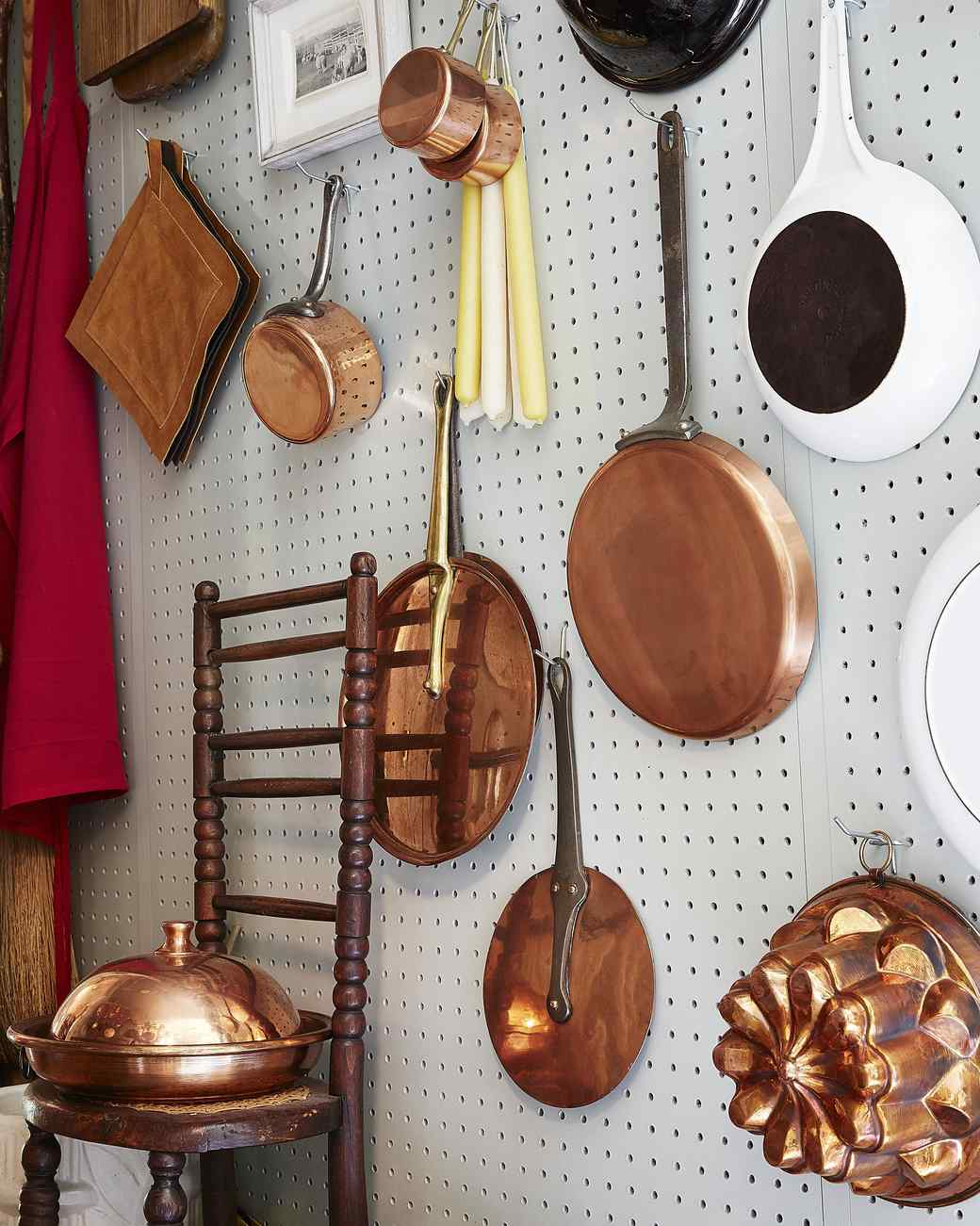 peg board wall with assortment of copper and ceramic wares