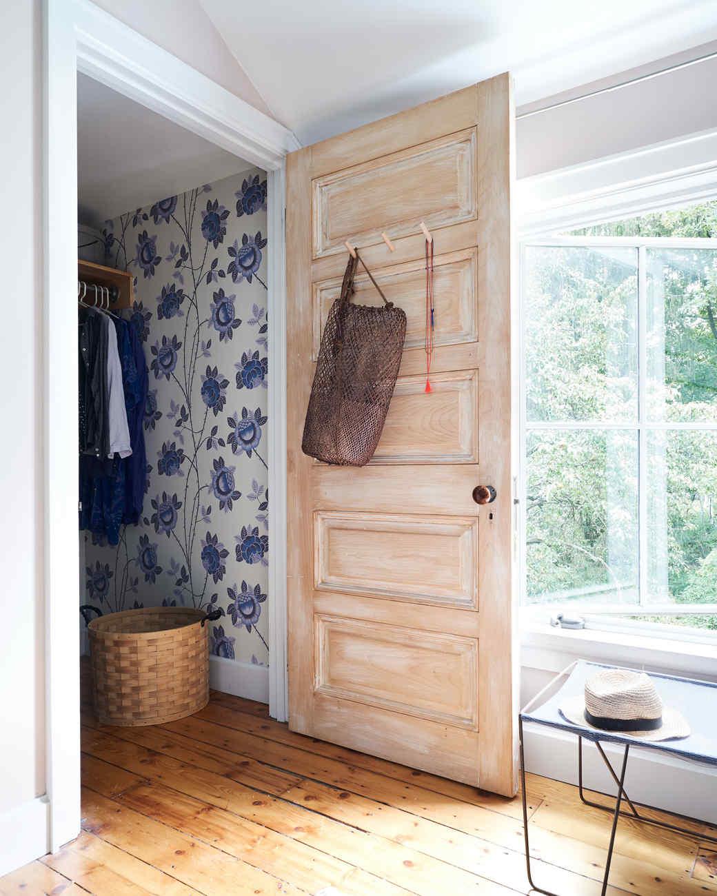 bedroom closet with refurbished door and blue floral wallpaper