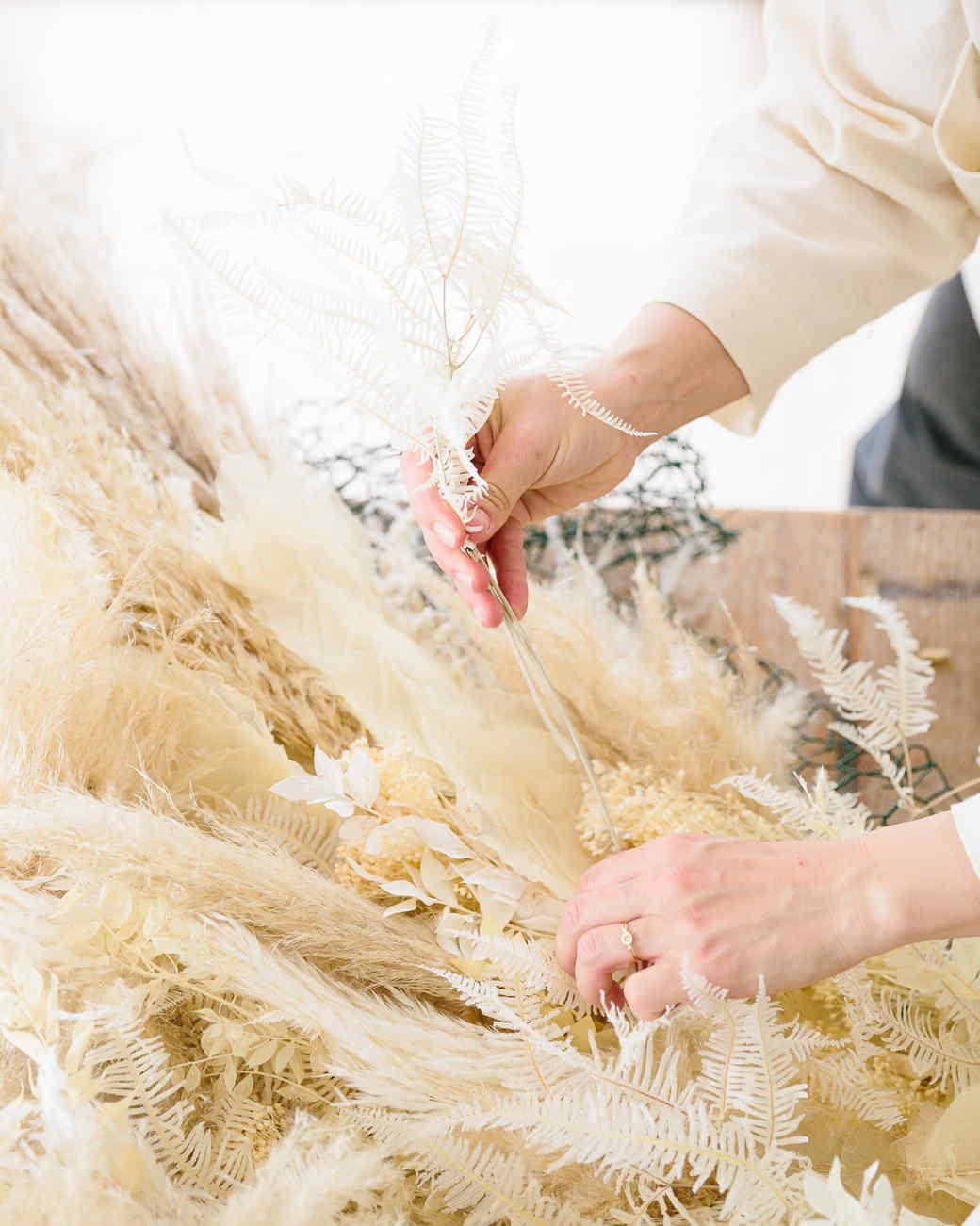 hands attaching pampas grass to chicken wire