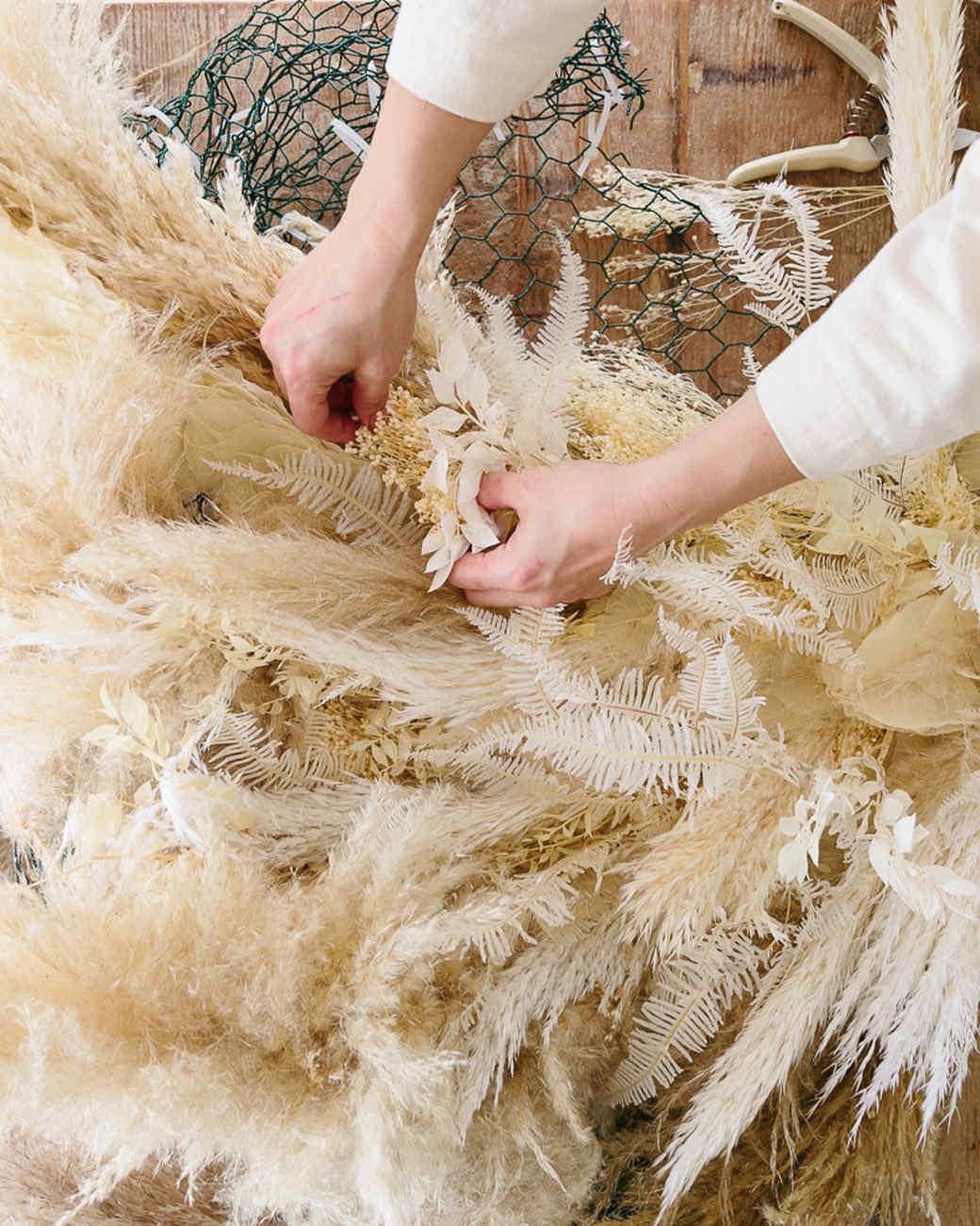 hands arranging pampas grass to chicken wire