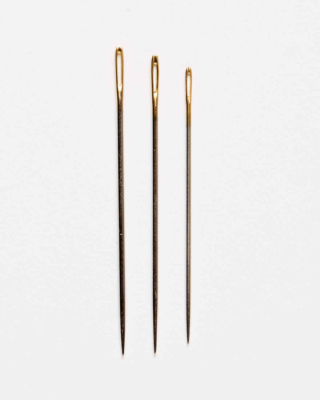 three embroidery quilting needles against a white background