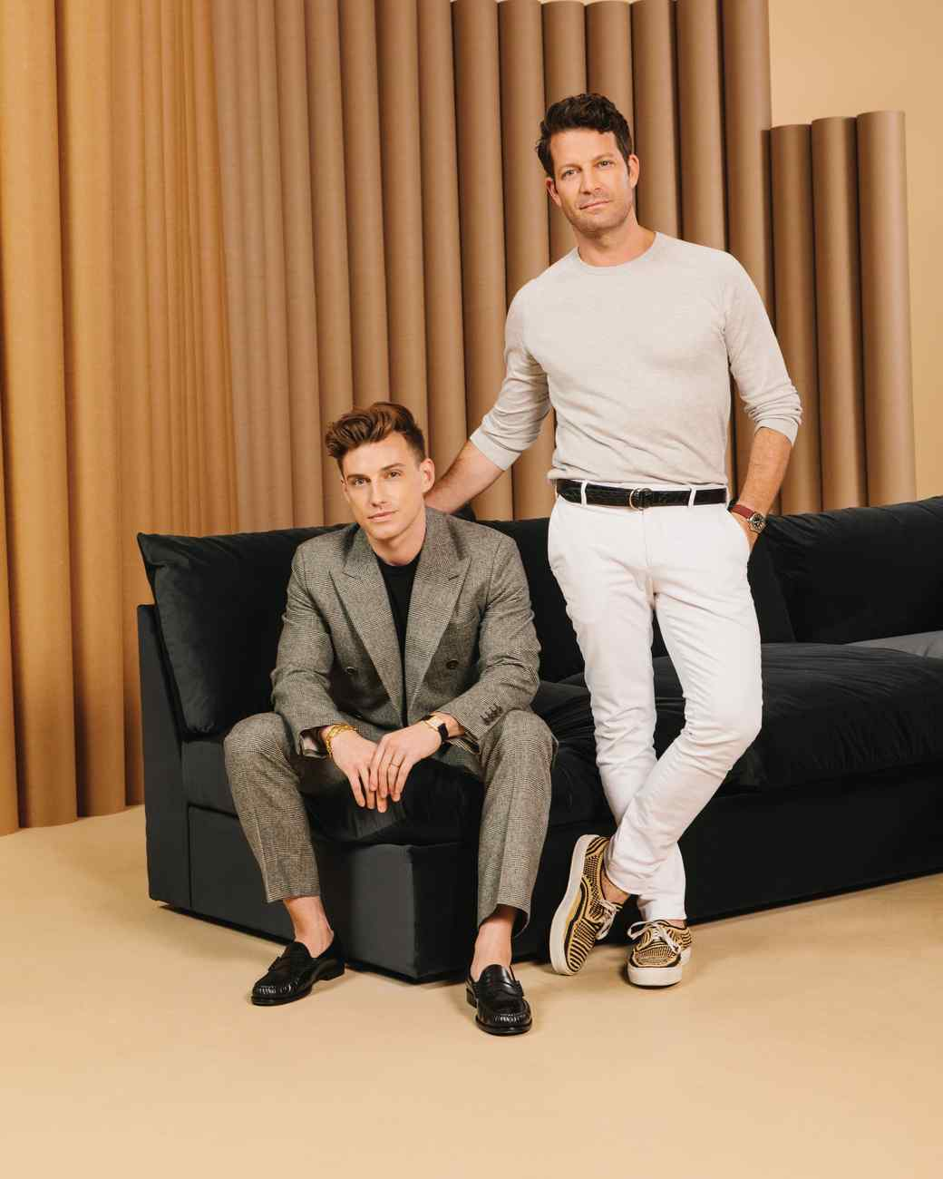 Nate Berkus and Jeremiah Brent in front of a sofa they designed for Living Spaces.