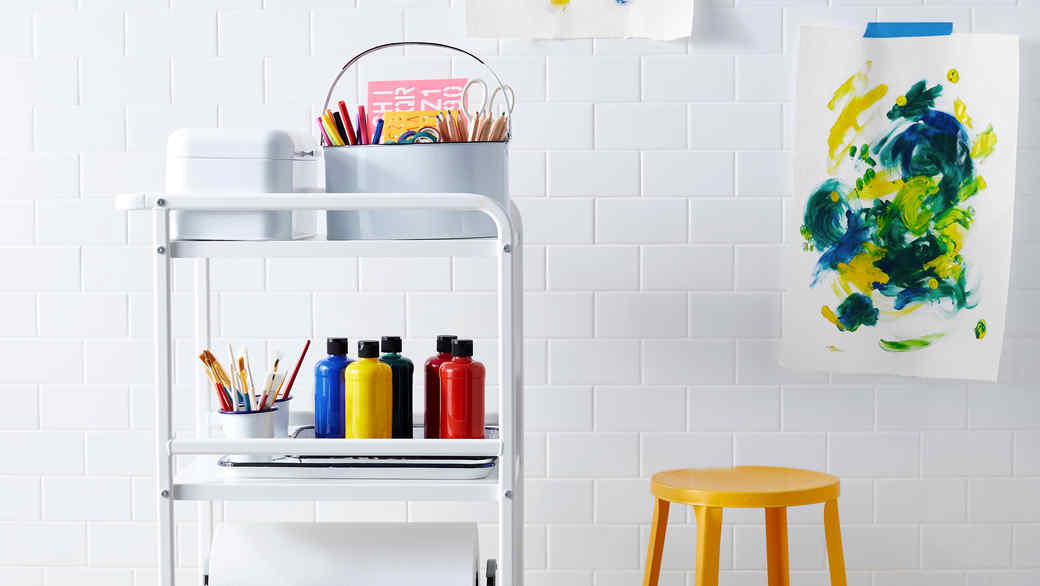 arts and crafts cart with kids paintings on wall