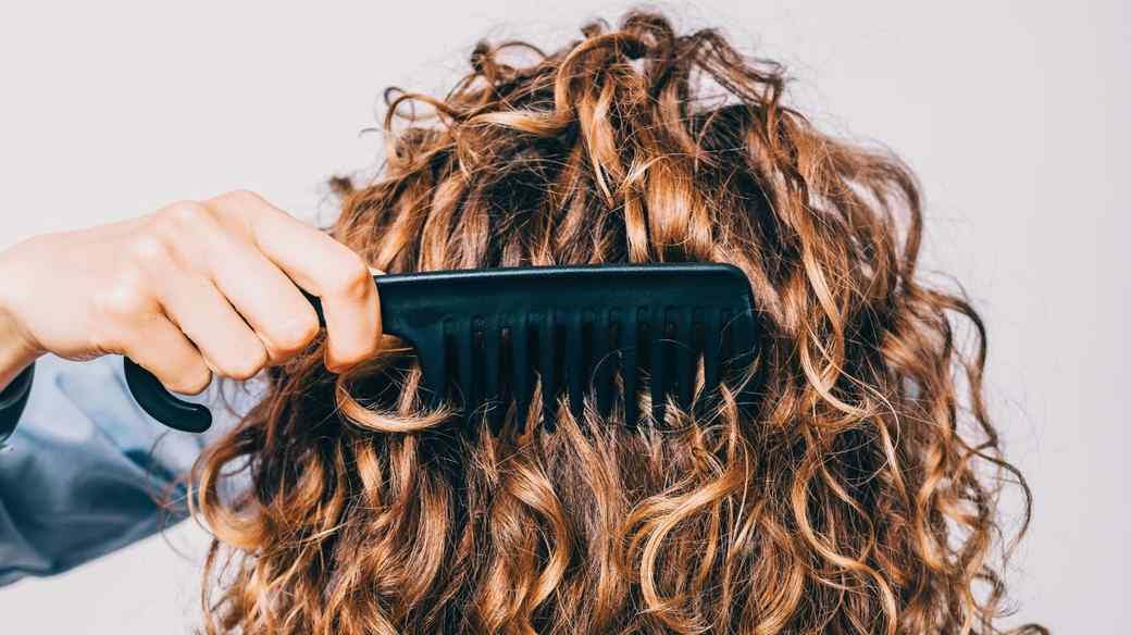 woman combing curly hair