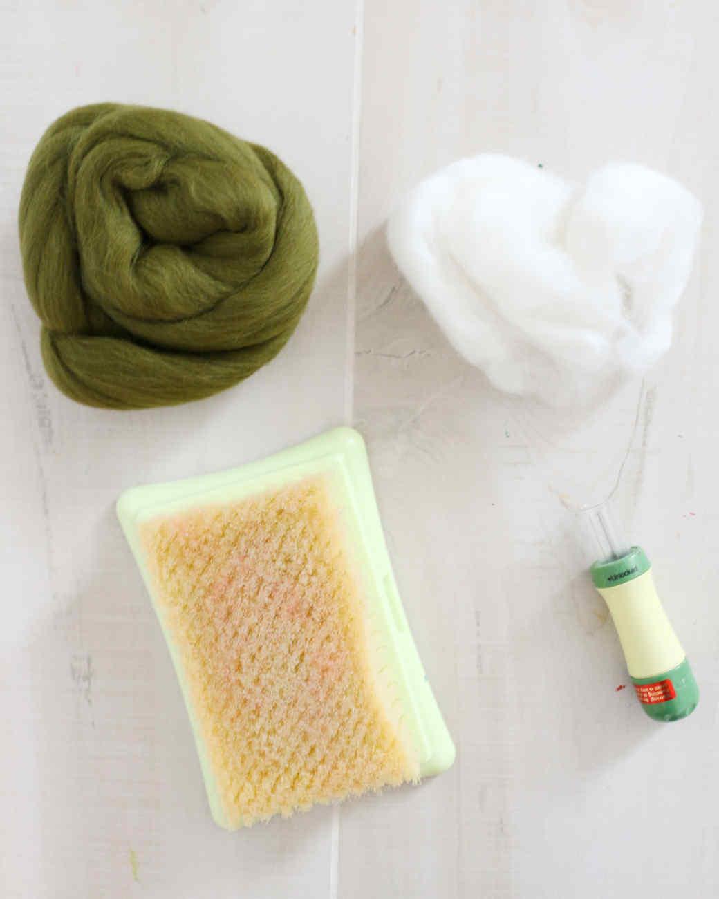 green and white felt, felting needle, and felting mat