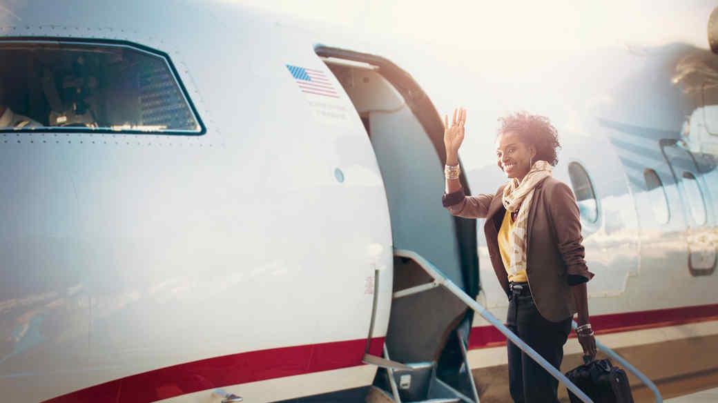 Woman waving as she boards small plane