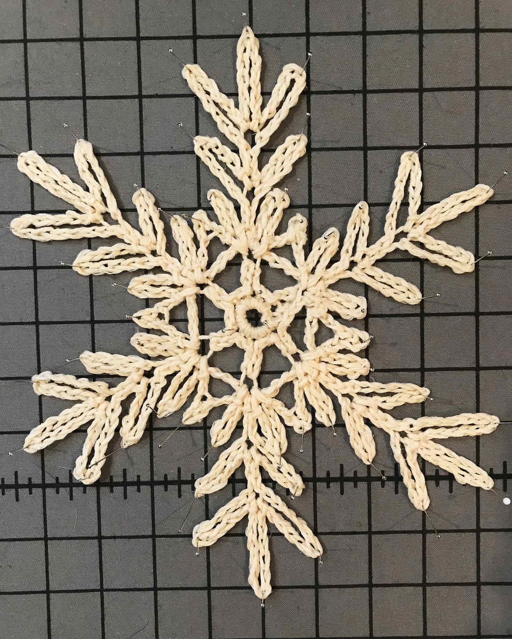 branch-like crochet snowflake pattern 4 on grid background with pins