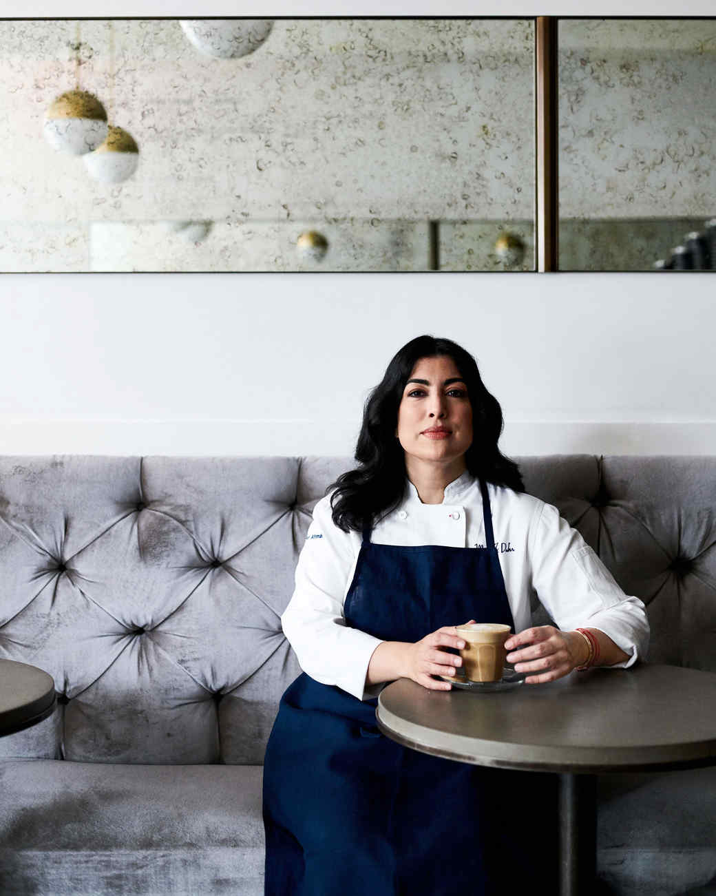 portrait of pastry chef umber ahmad sitting with a cappuccino