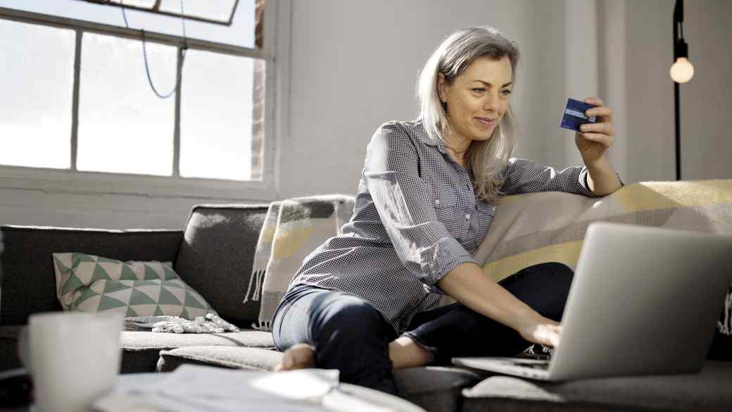 woman holding debit card while using laptop on sofa