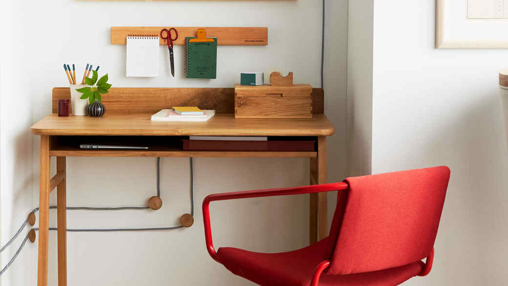 wood office desk with red chair on wheels
