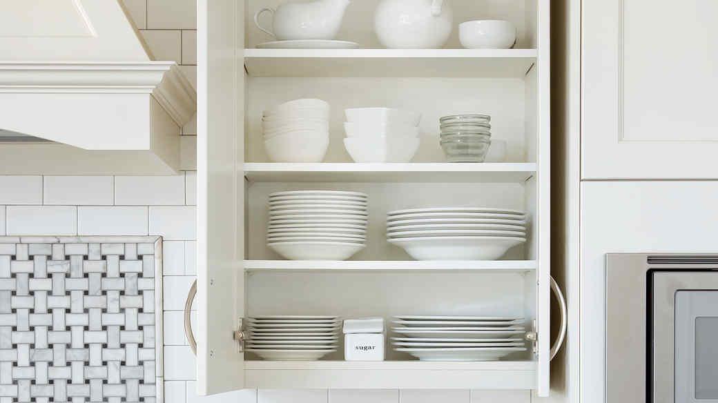 organized white dishes cabinet in kitchen