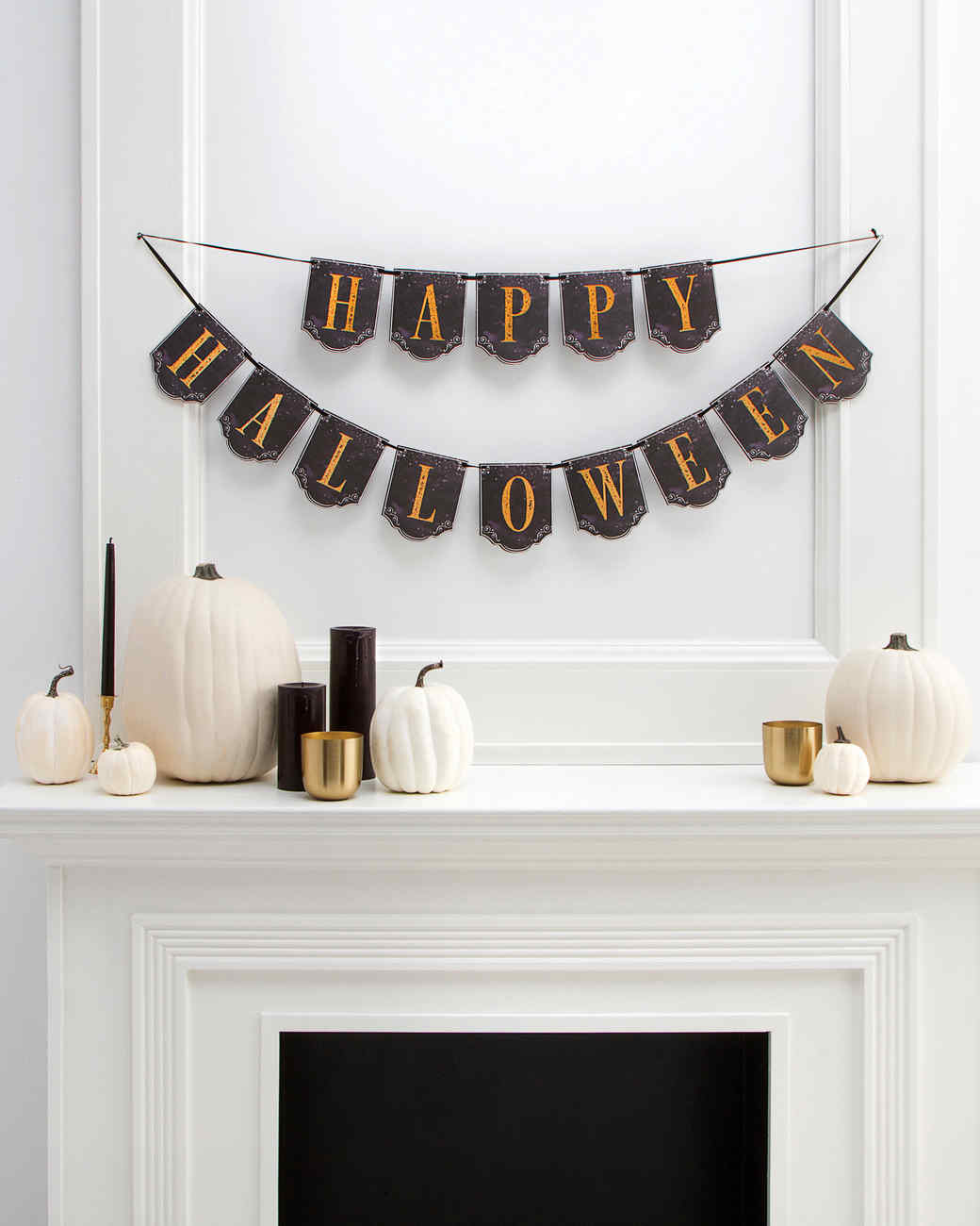 halloween banner and white pumpkins and black candles with gold accents on mantel