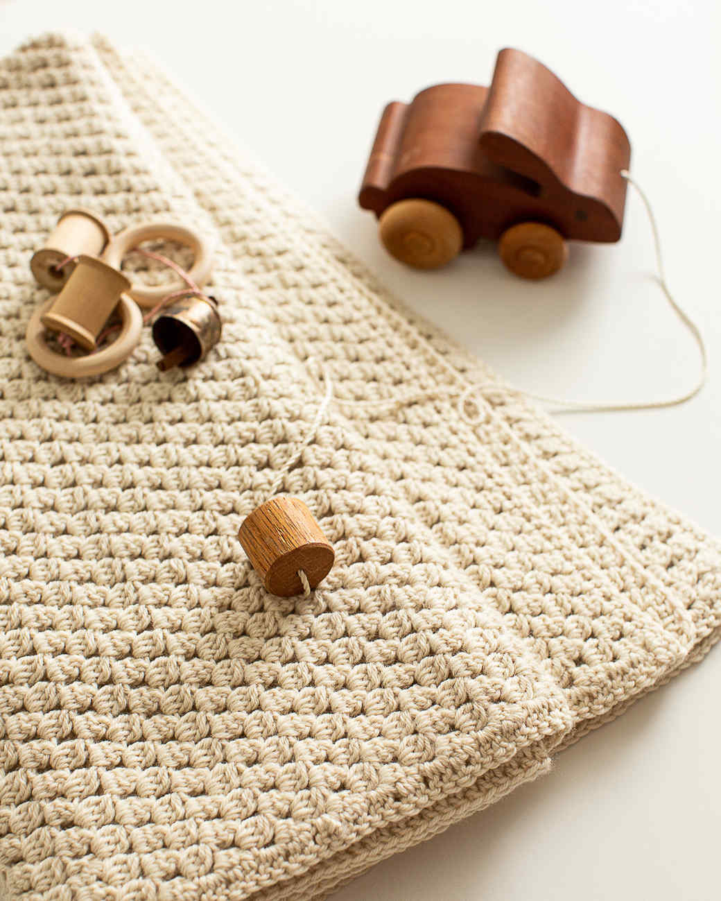 soft bobble crocheted baby blanket with wooden toys