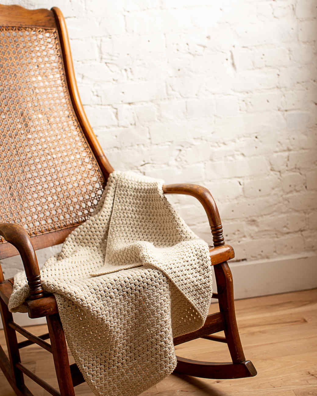 soft bobble crocheted baby blanket draped over a chair