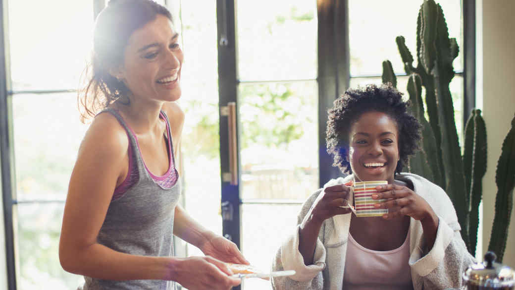 two women laughing at breakfast table