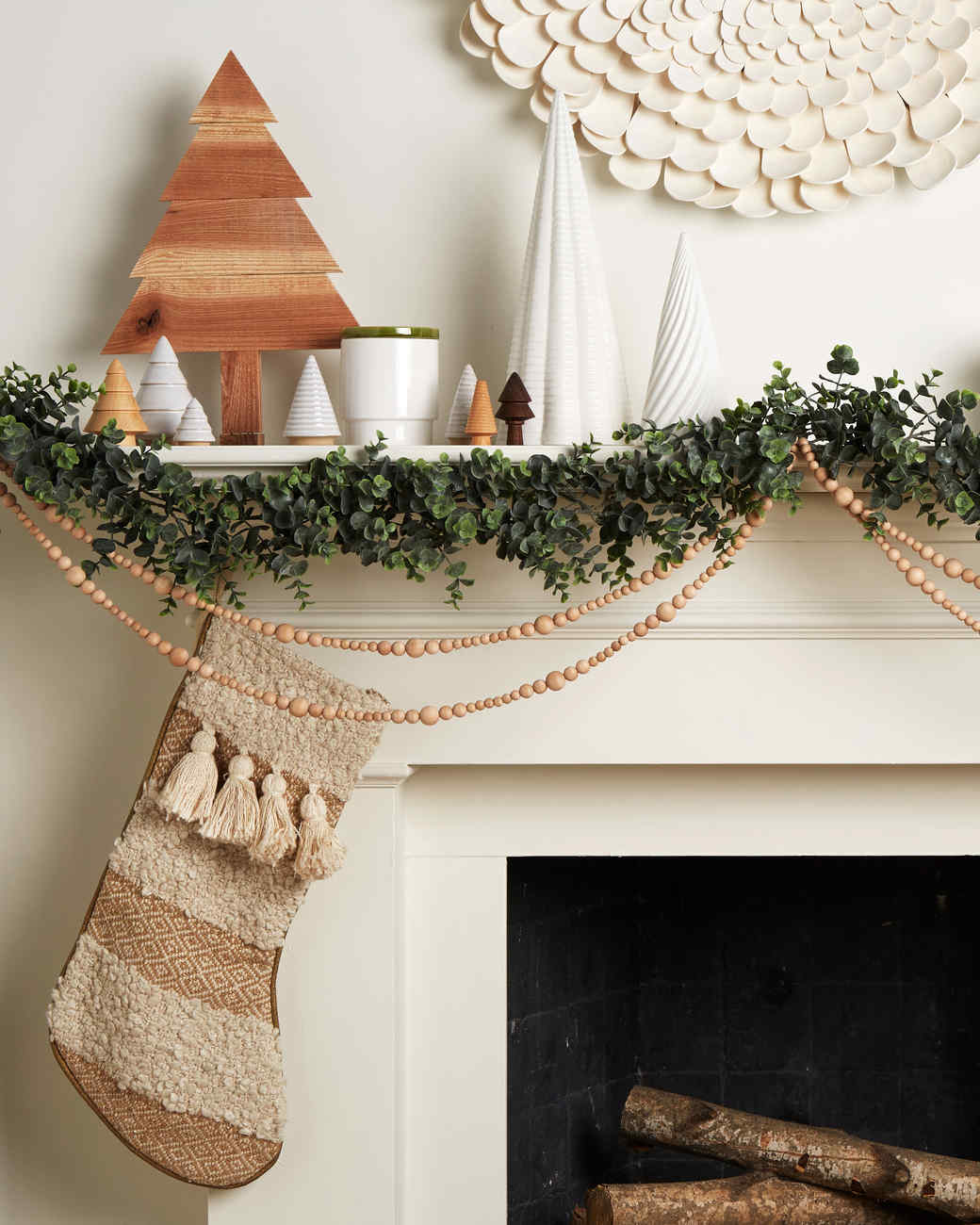 Scandinavian-inspired mantle white with wooden beaded garland greenery and trees