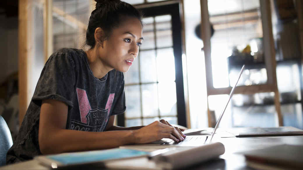 woman leaning over laptop computer getty