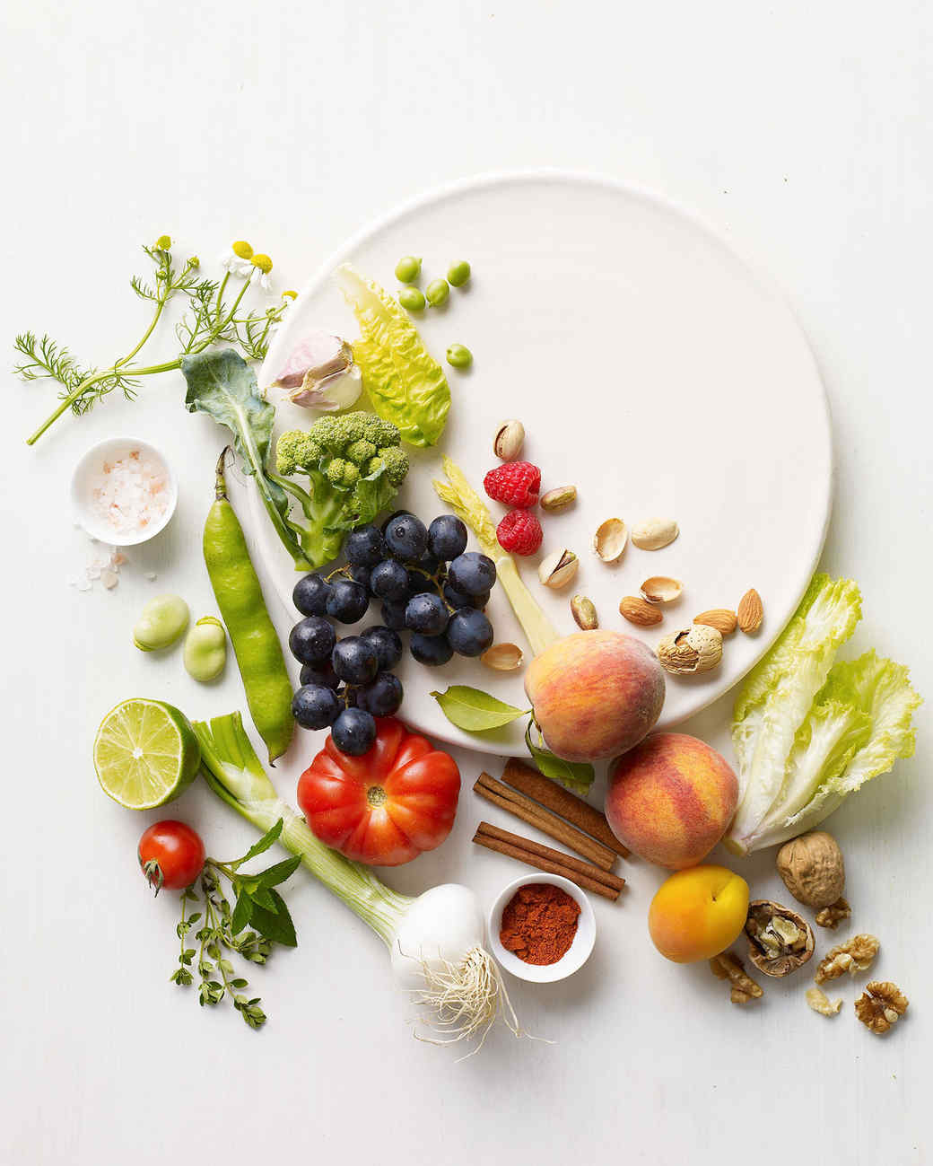 an assortment of fruits and vegetables on a white plate