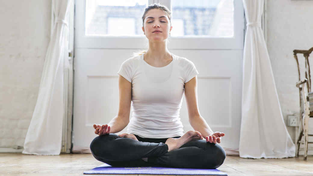 brunette woman meditating on yoga mat