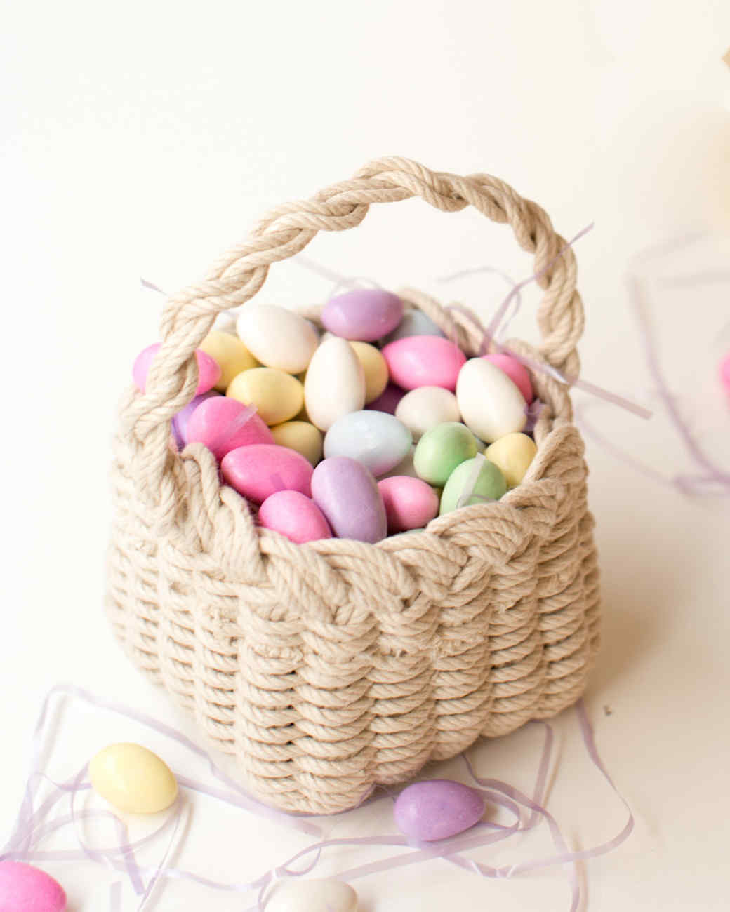 A handwoven Easter basket with pastel candy eggs.