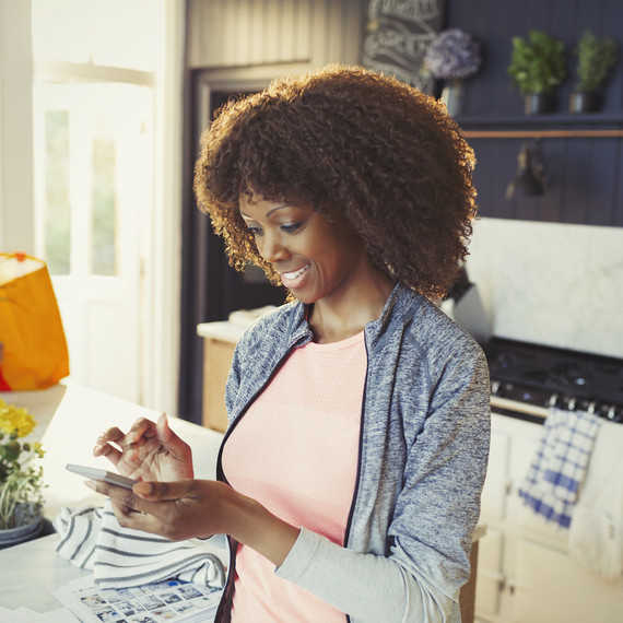 A woman smiles while looking at her cell phone.