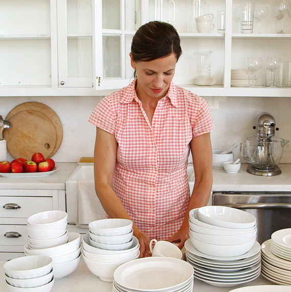woman organizing white dishes in kitchen