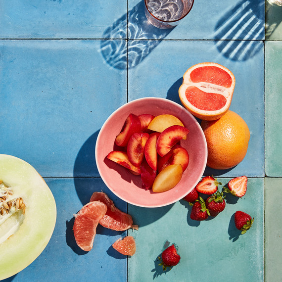 pink fruit and honey dew on blue tile