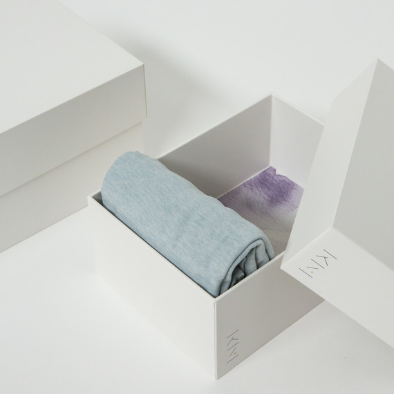 white marie kondo box with clothes folded in it