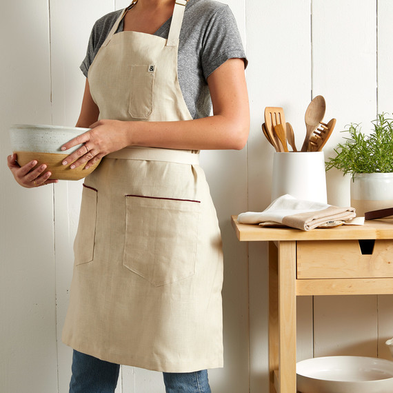 woman in tan apron holding ceramic bowl