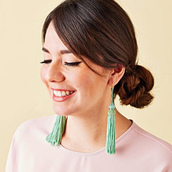 green fringe earrings on woman