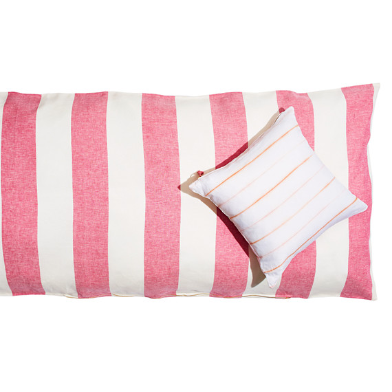 pink and white throw bed with pillow