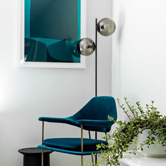 blue velvet chair and double bulb standing lamp in corner of room