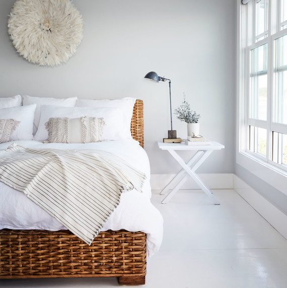 white bedroom with rattan bed