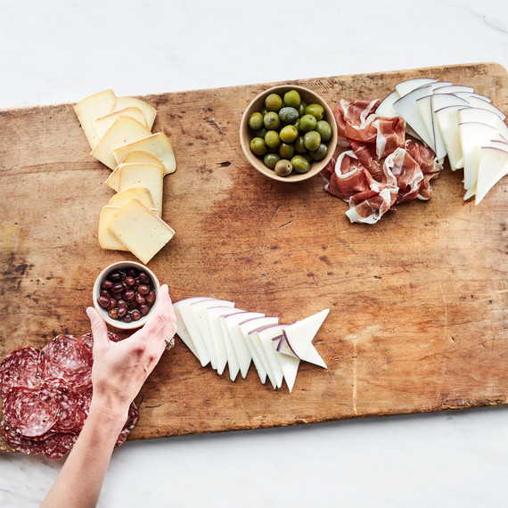 grazing board summer step 4 meats dips cheese wooden hand holding olives