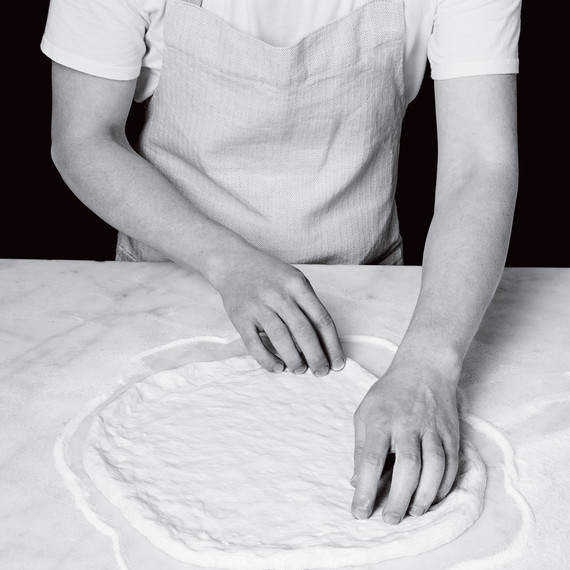 spreading out pizza dough