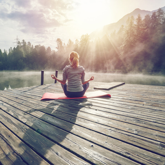 Woman Sitting on a Dock Doing Exercise in the Morning