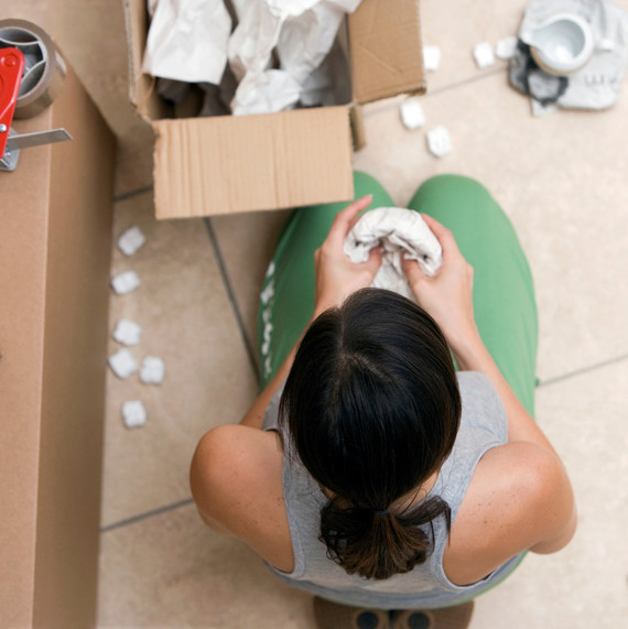 overhead of woman wrapping dishes