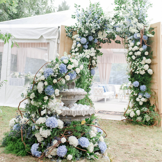 charitable baptism celebration white flower arch and flowered fountain outside of tent